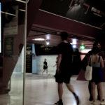 APAC News commuters in Sydney train station walk past coronavirus headline